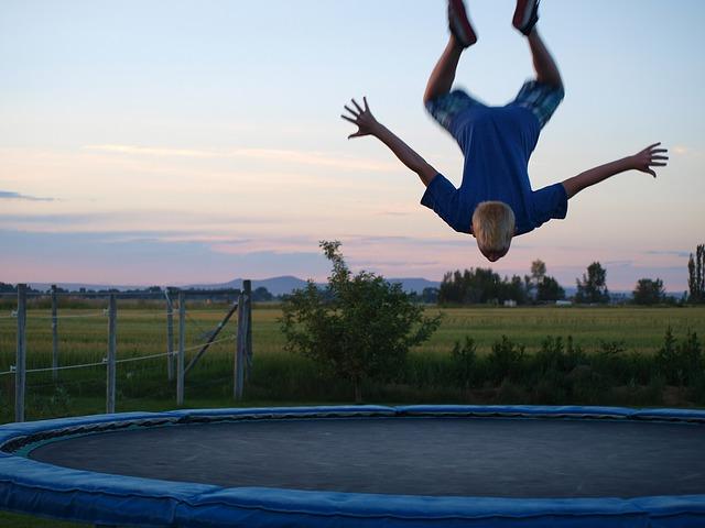 chlapec vzhůru nohama, trampolín,a skok