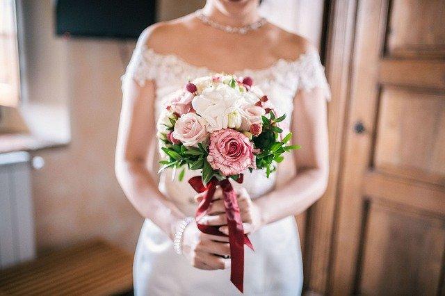 nevěsta držící kytici červených růží
